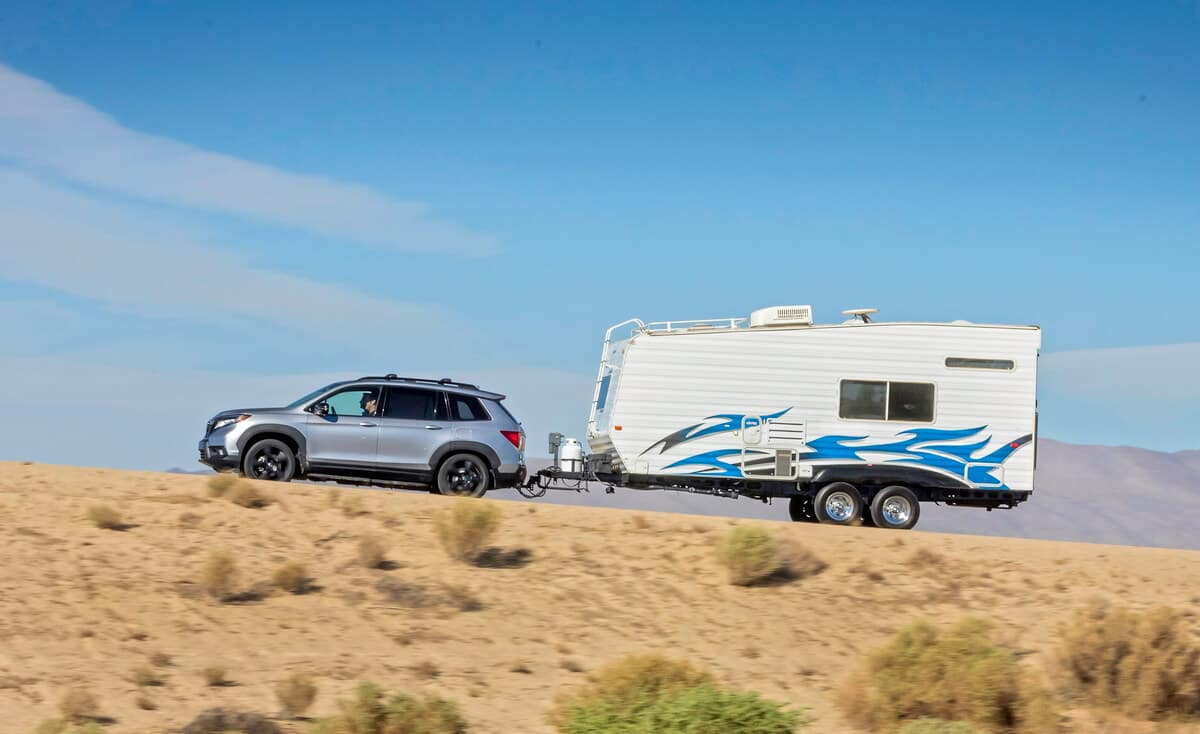 Side view of 2020 Honda Passport pulling large white trailer