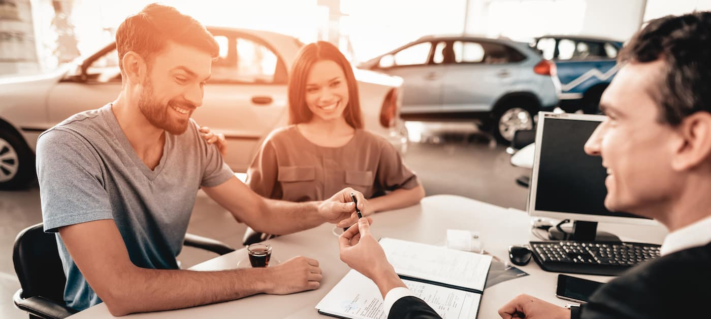 Happy Young Family Are Signing A Contract To Buy A Car. Dialogue With Dealer. Cheerful Customer. Automobile Salon. Make A Decision. Cup Of Coffee. End Of A Deal. Good Offer. Buyer And Seller.