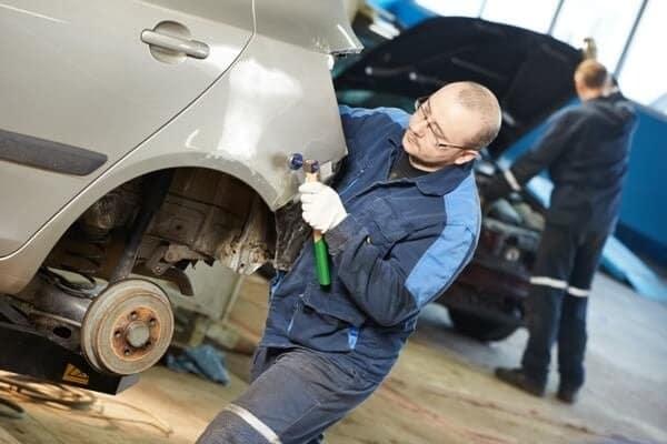 Mechanic Fixing Vehicle in Shop