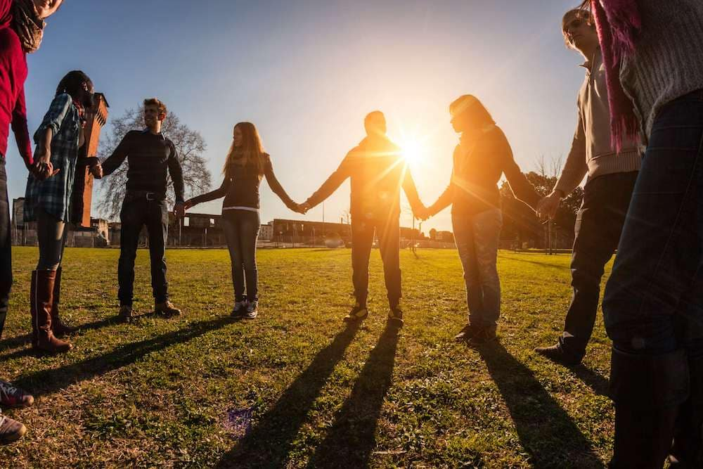 Group of young people hold hands in front of sunrise