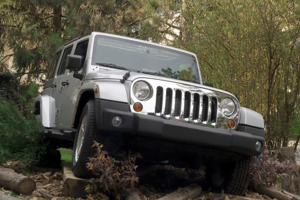 Silver Jeep off-road in woods