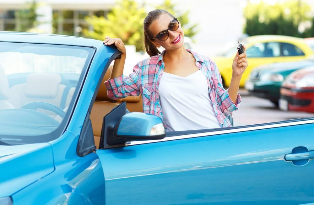a photo of a young woman next to her used car with keys in her hand