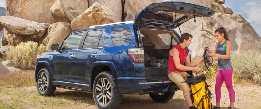 A man and a woman sit on the open liftgate of a blue 2019 Toyota 4Runner