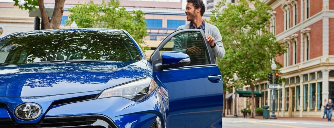 Man getting out of blue 2019 Toyota Corolla on street corner