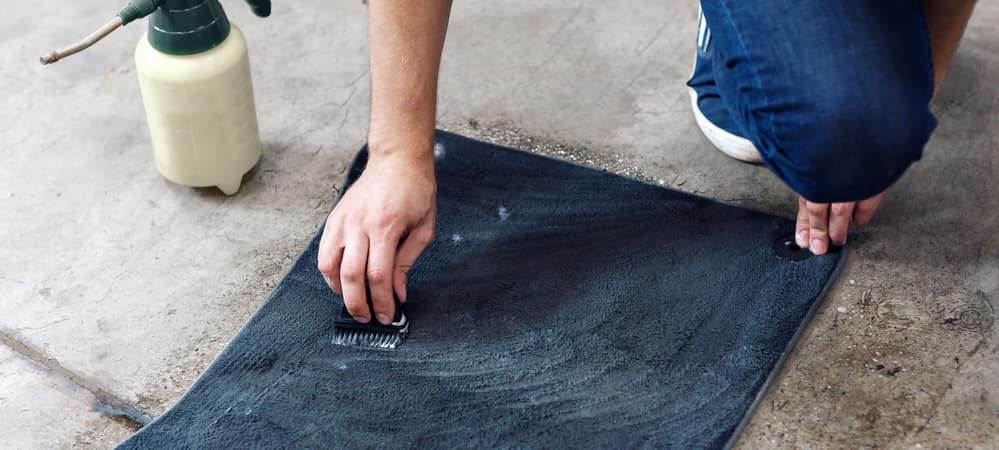 Close of up of a person scrubbing a floor mat with cleanser on the ground