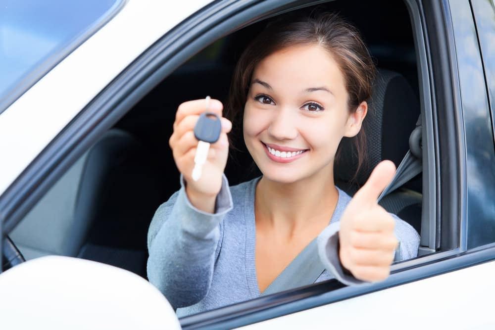 Woman holding up car key with thumb up