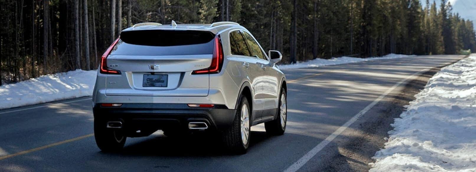 2019 Cadillac XT4 driving down road rear view