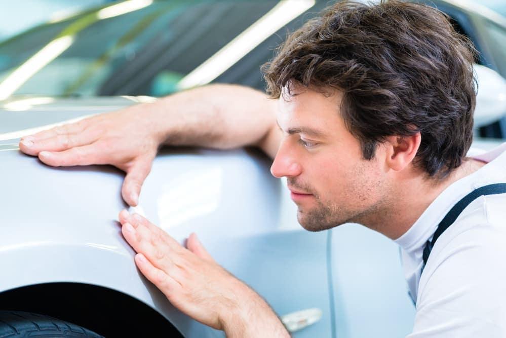 Man reviews car fender dent