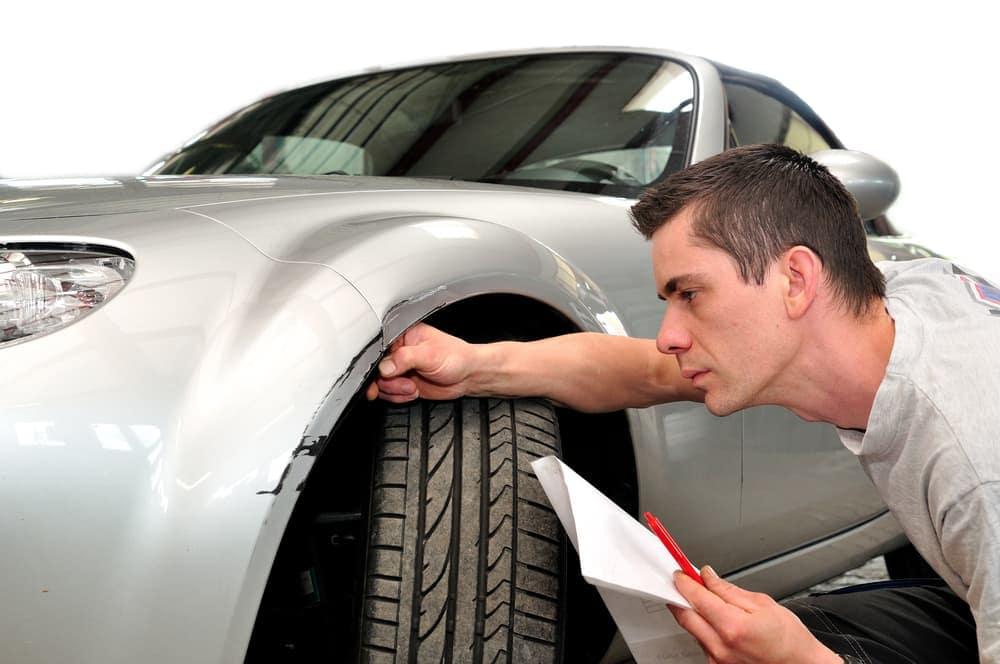 Man reviews scratch on car fender