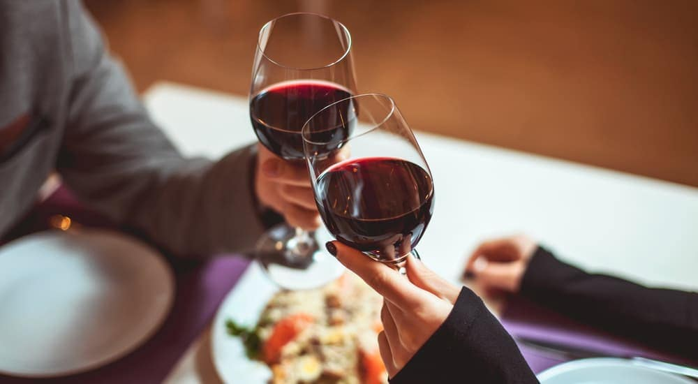 A couple is clinking wine glasses over an Italian meal in Joliet, IL.