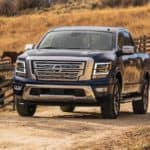 A dark blue 2021 Nissan Titan is driving past horses on a dirt road and shown from the front.