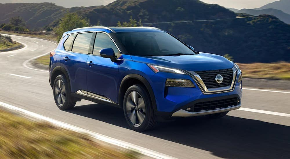 A blue 2021 Nissan Rogue is driving on a winding road past mountains.