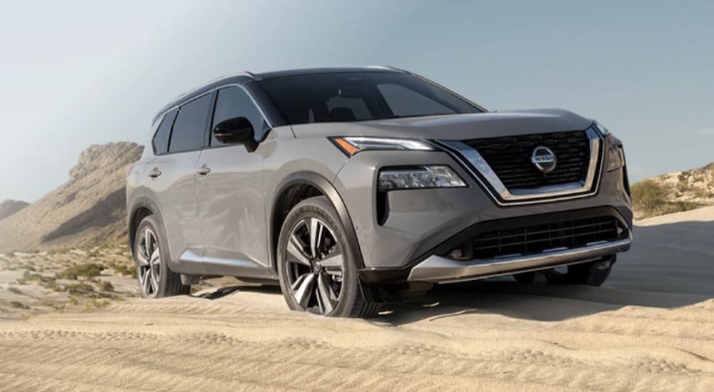 A popular Nissan SUV, a grey 2021 Nissan Rogue, is parked on a sand dune.