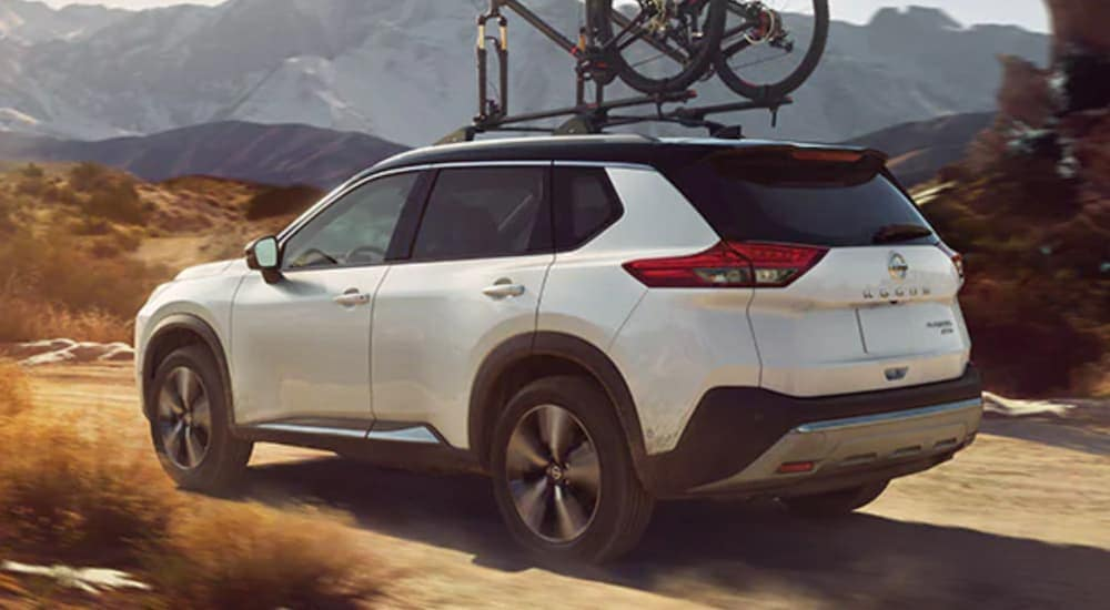 A white 2021 Nissan Rogue with bikes on the roof is driving on a dirt road in front of a distant mountain.