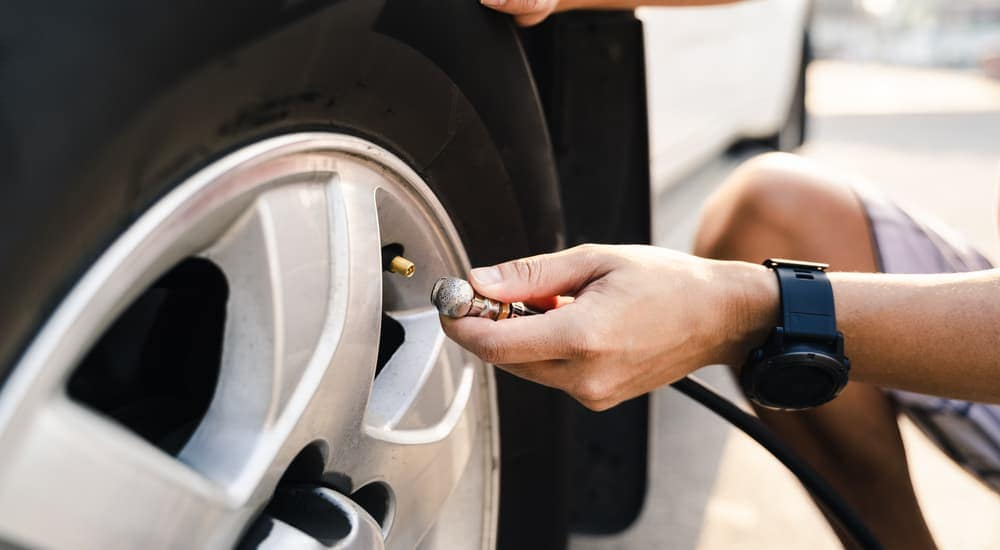 A person is attaching a nozzle to fill a tire with air.