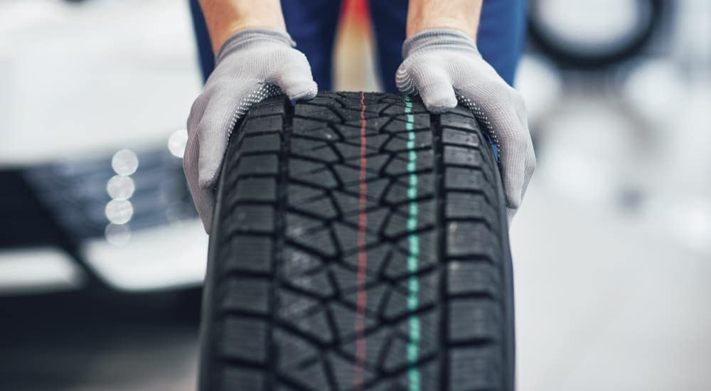 Gloved hands are holding a tire with colored markings on it at a tire shop.