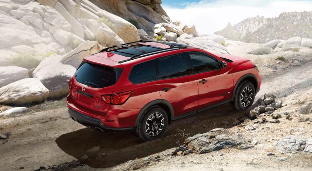 A red 2021 Nissan Pathfinder is driving down a rocky path after leaving a Chicagoland Nissan dealer.