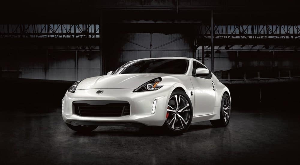 A white 2020 Nissan 370z is parked in a dark warehouse.