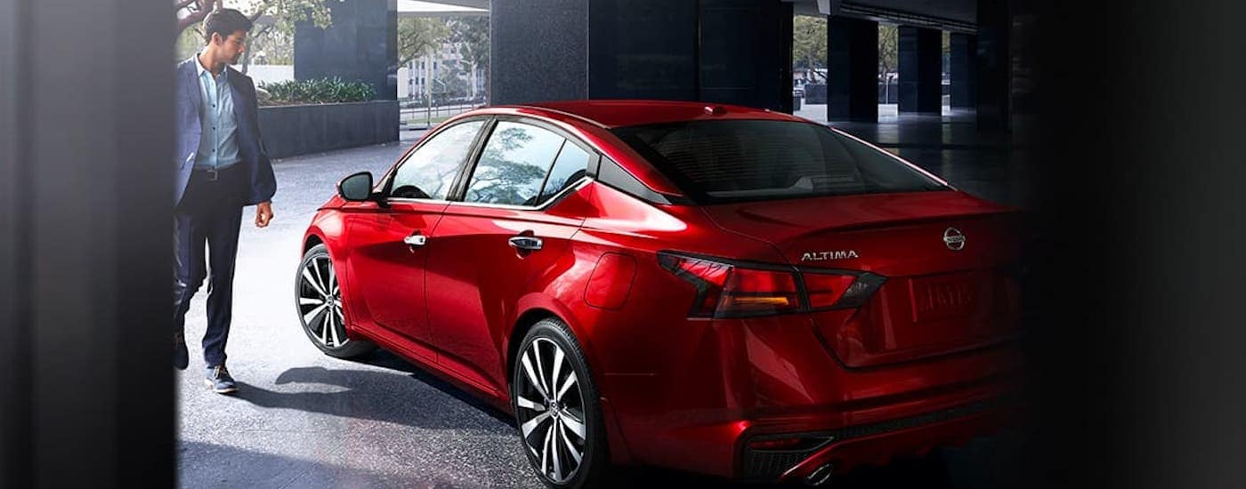 A man is walking towards a red 2021 Nissan Altima in front of a stone building.