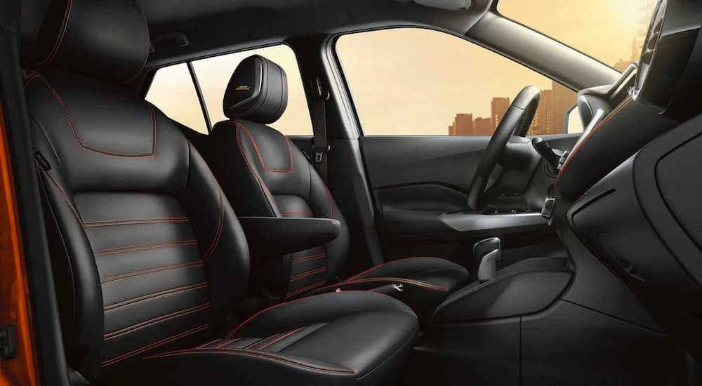 A close up from the passenger side shows the black front seats of a 2021 Nissan Kicks.