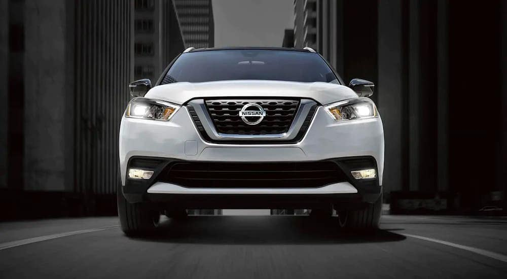 The grille of a white 2021 Nissan Kicks is shown from a low angle on a city street.