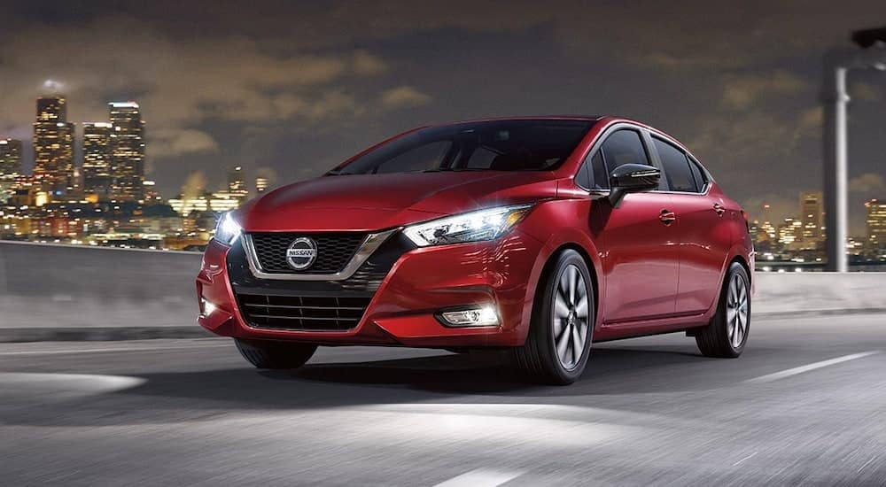 A red 2021 Nissan Versa is driving down the highway past the city after leaving a Joliet Car Dealership.