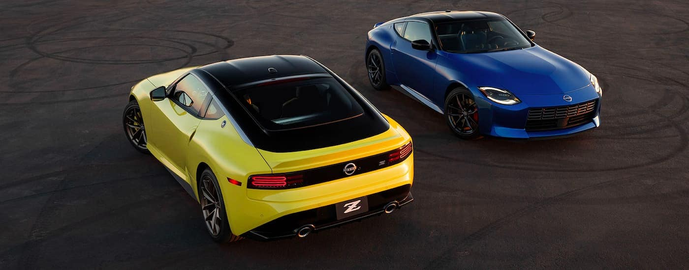 A yellow and a blue 2023 Nissan Z are shown parked facing in opposite directions on pavement with tire marks.