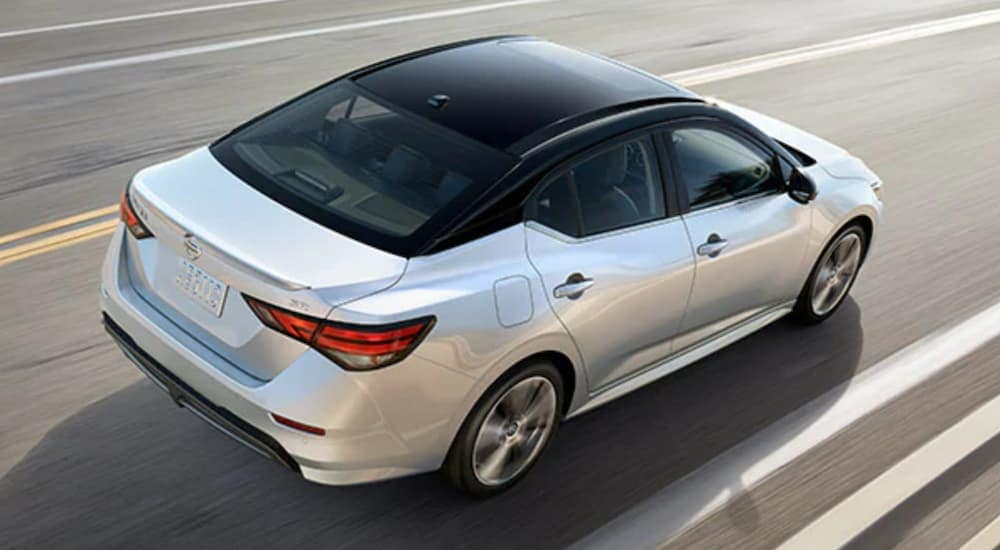 A white 2020 Nissan Sentra with a black roof is shown from above on a highway.