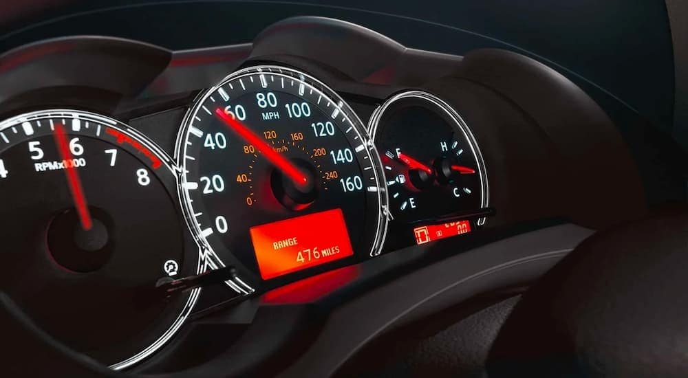 A close up shows the gauge cluster on a 2011 Nissan Altima.