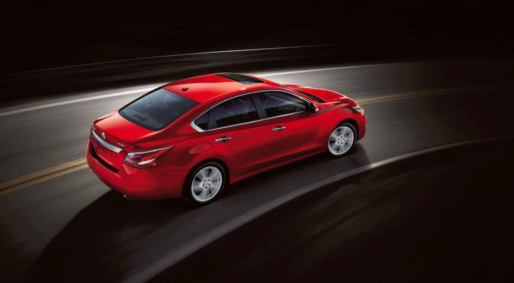 A red 2015 Nissan Altima is shown from the side, at a high angle, while driving around a bend.
