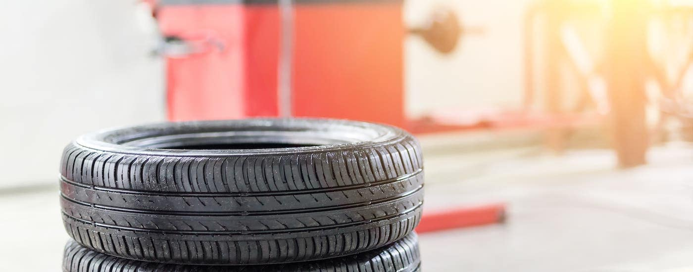 A stack of tires are shown in a garage of a Nissan service center.