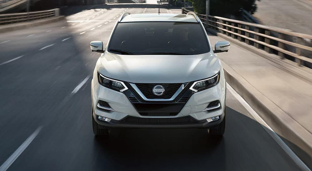 A white 2021 Nissan Rogue Sport is driving on a city highway.