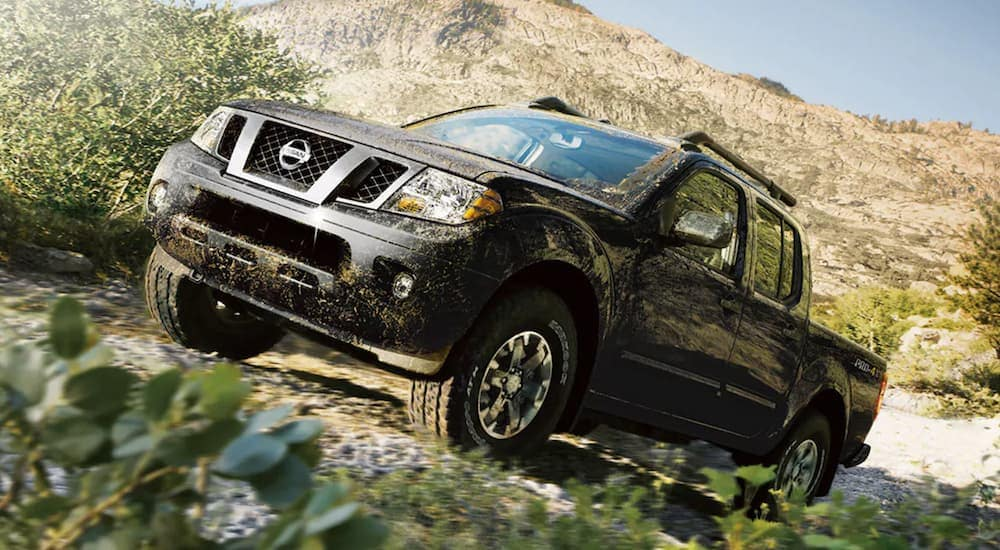 A black 2021 Nissan Titan is off-roading on a hill.