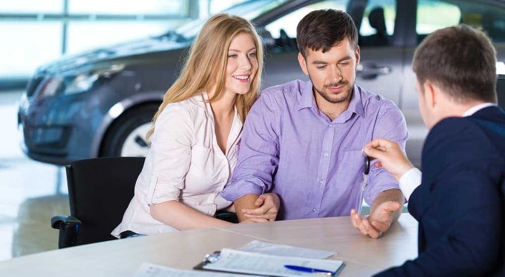 A salesman is talking to a couple about Nissan lease deals.