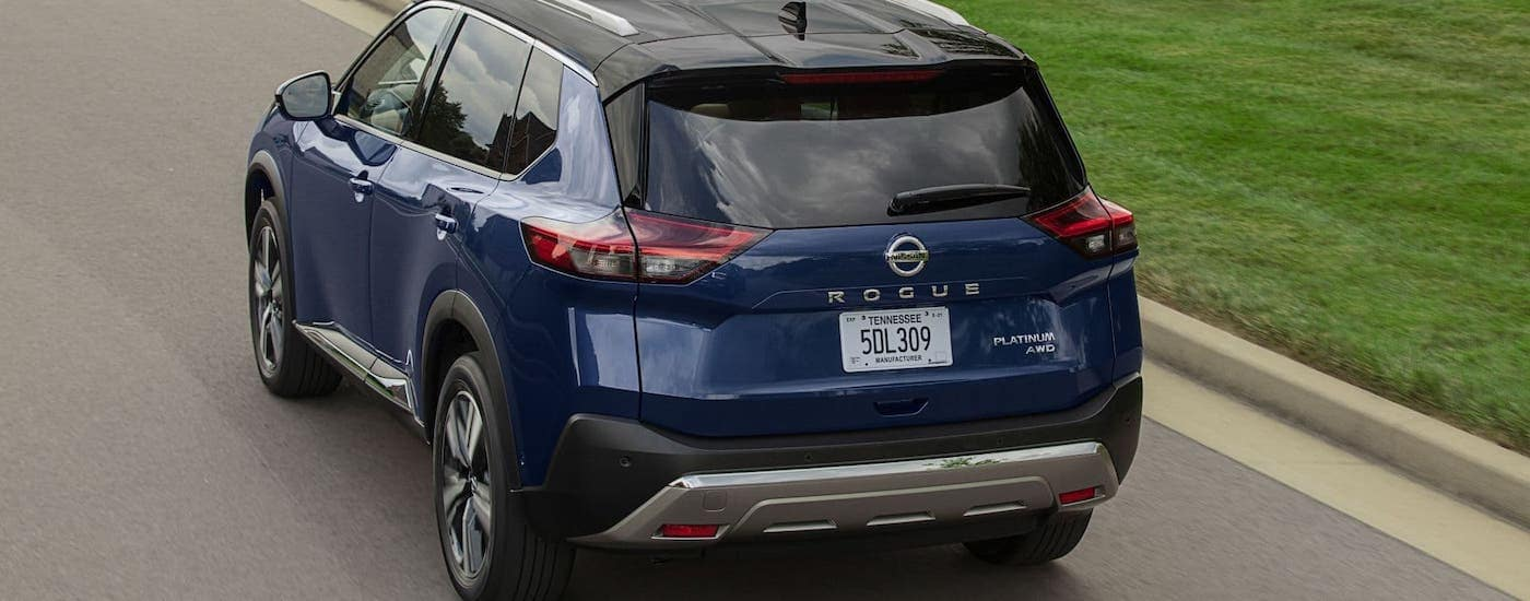 A blue 2021 Nissan Rogue is shown from the rear driving on a street.