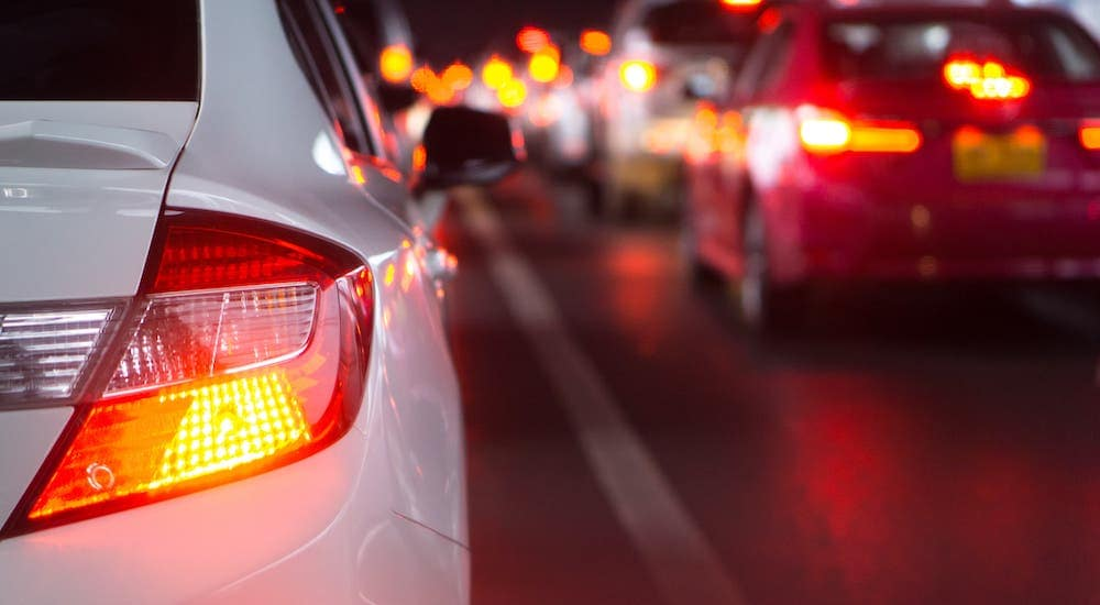 A closeup shows the brake light on a white sedan driving in the city at night.