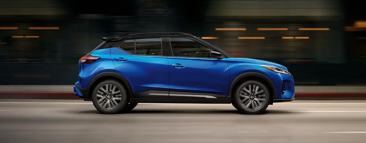 A blue 2021 Nissan Kicks is shown from the side on a multi-lane road with a blurred background.