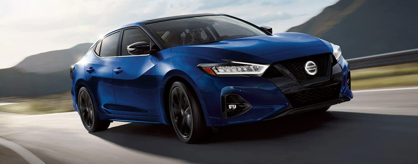 A blue 2021 Nissan Maxima is driving on a rural road with blurred mountains.