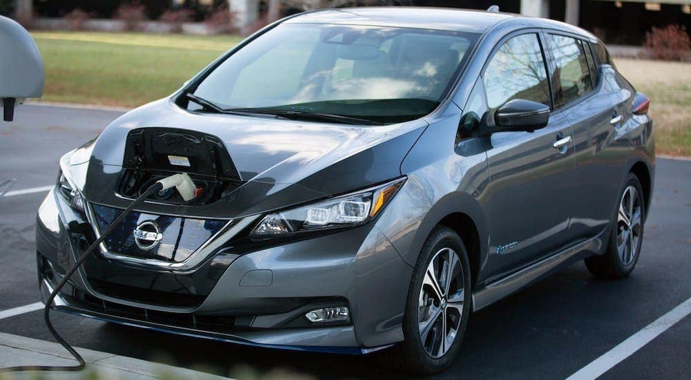 A gray 2021 Nissan LEAF is charging in a parking lot.