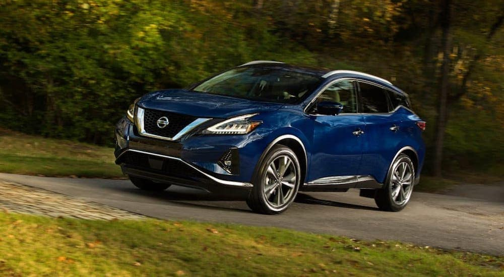 A blue 2021 Nissan Murano is driving in front of trees as part of a Nissan end of lease test drive.