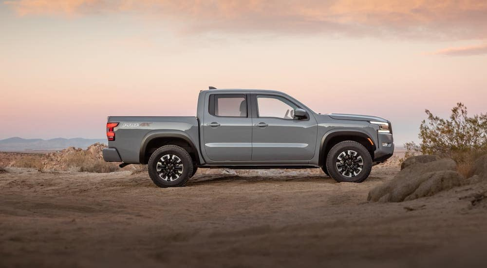 A gray 2022 Nissan Frontier is shown from the side in front of a desert and pink skies.