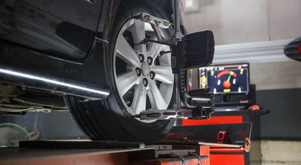 A wheel alignment is being performed on a black car.