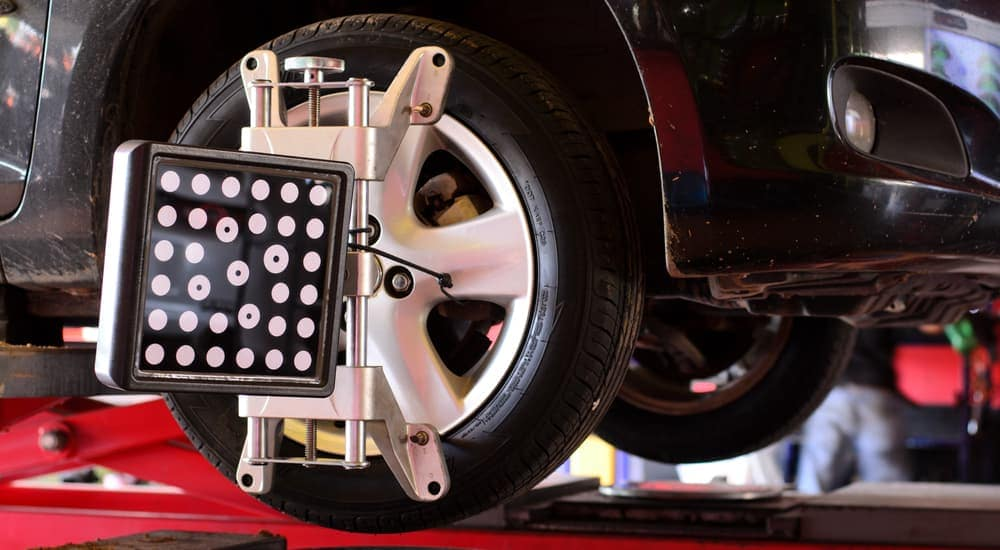 A wheel is shown with an alignment calibrater on a black car.