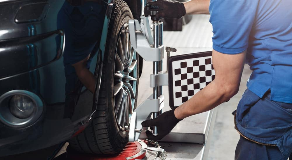 A mechanic is setting up a wheel alignment on a black car.