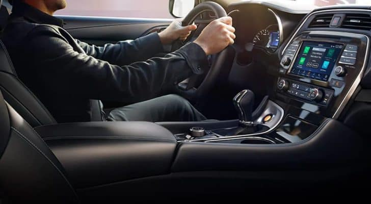 A popular model at Joliet car dealers, a 2021 Nissan Maxima, is shown from the interior with the infotainment system and a man at the wheel.