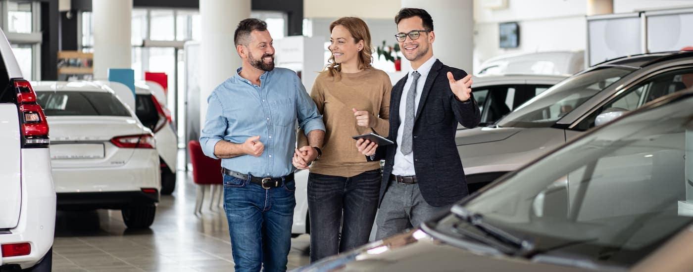 A close up shows a couple and a salesman at a Joliet car dealer.