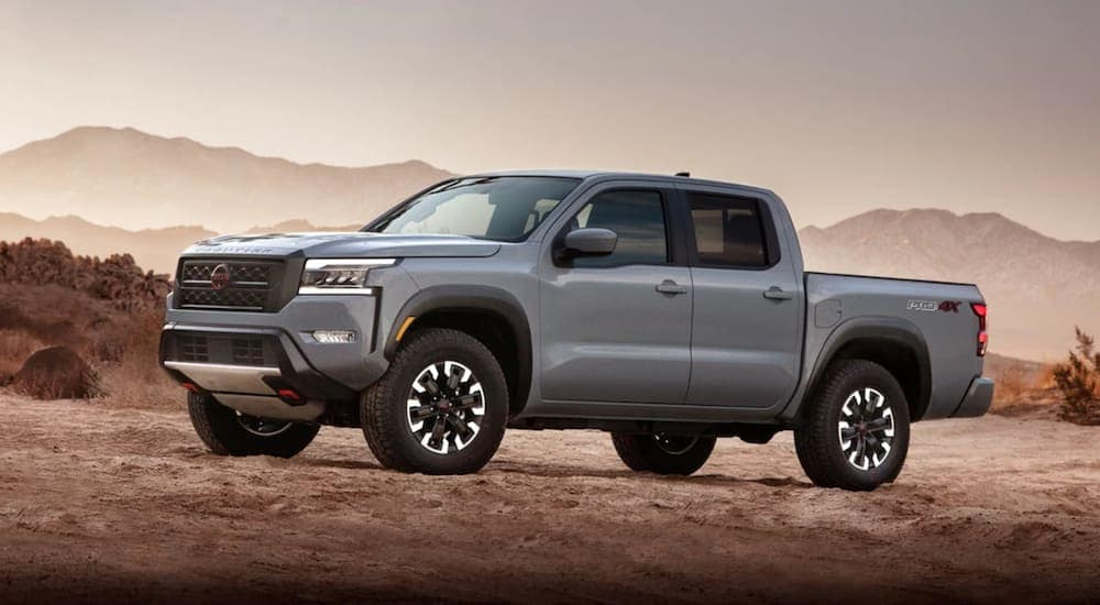 A grey 2022 Nissan Frontier is parked in a desert.