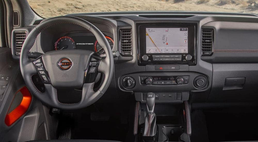 The interior of a 2022 Nissan frontier shows the steering wheel and infotainment screen.