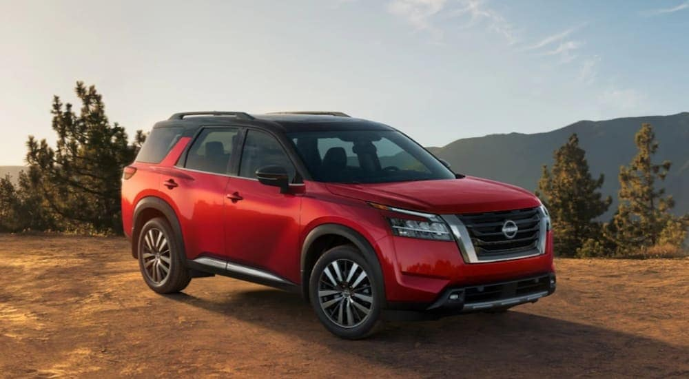 A red 2022 Nissan Pathfinder is parked on a mountain after leaving Joliet car dealers.