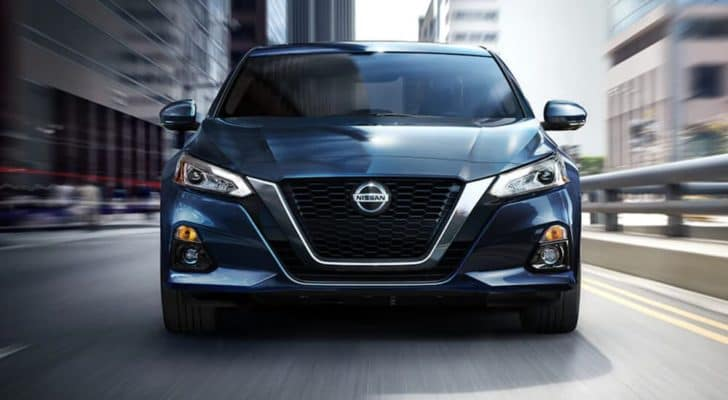 A blue 2021 Nissan Altima is driving on a city street, shown from the front.